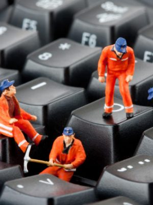 Small figurines of workers repairing computer keyboard